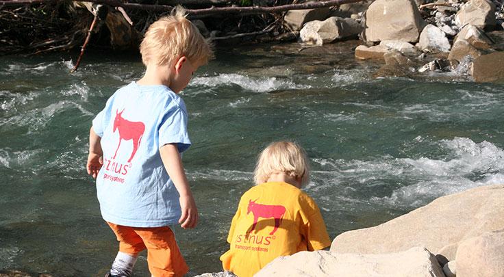 Zwei Kinder in Firmen-Shirts spielen am Wasser
